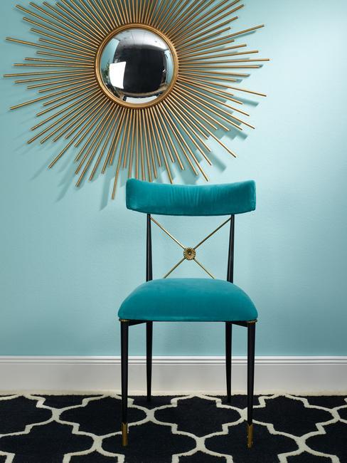 Een stoel met een decoratieve gouden spiegel aan de muur in een eclectische stijl