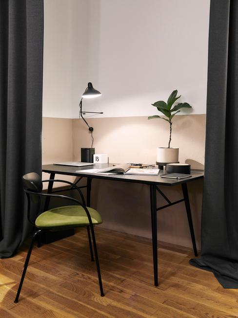 zwart bureau met een zwarte stoel met groen kussen