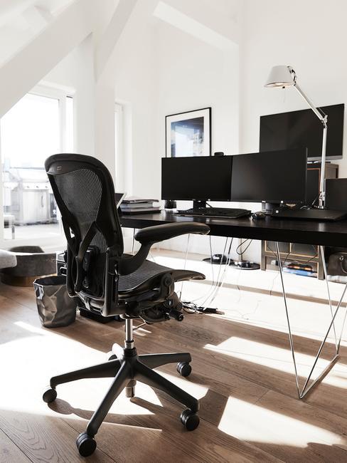zwarte bureau met een zwarte bureaustoel en 2 beeldschermen