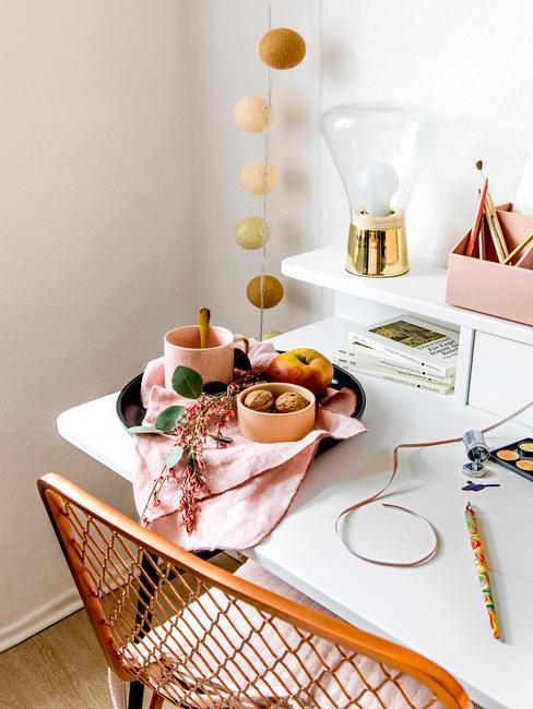 wit bureau met een gouden stoel en gekleurde mokken