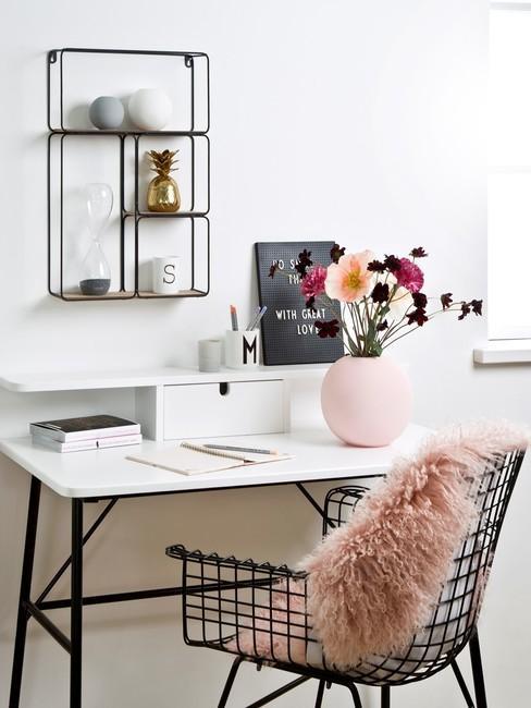 wit bureau met een zwarte stoel en roze kussen
