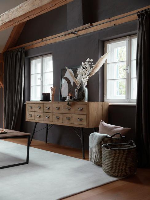 houten wandtafel tegen grijze muur met vazen en droogbloemen
