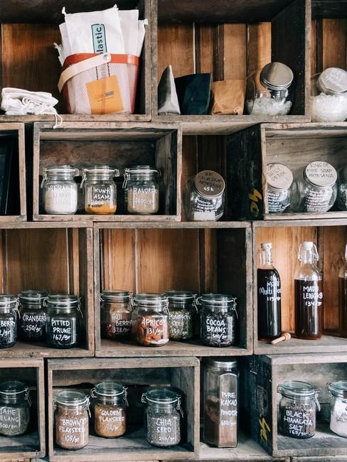 Houten voorraadkast met glazen potten met kruiden