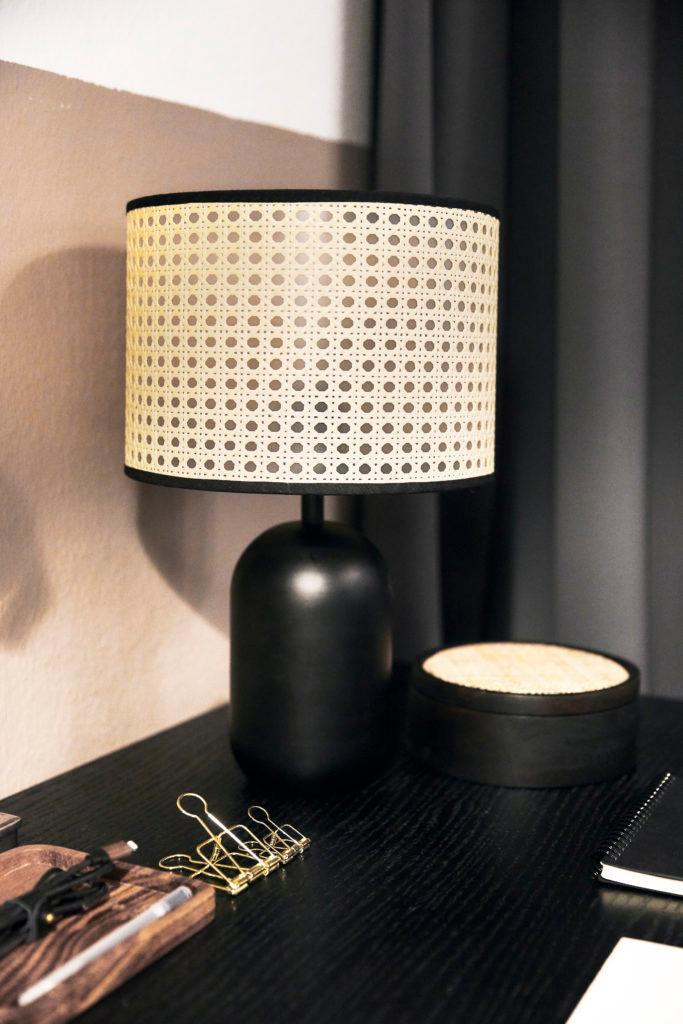 Zwarte tafellamp met rotan lampenkap op zwarte bureau in feng shui kantoor