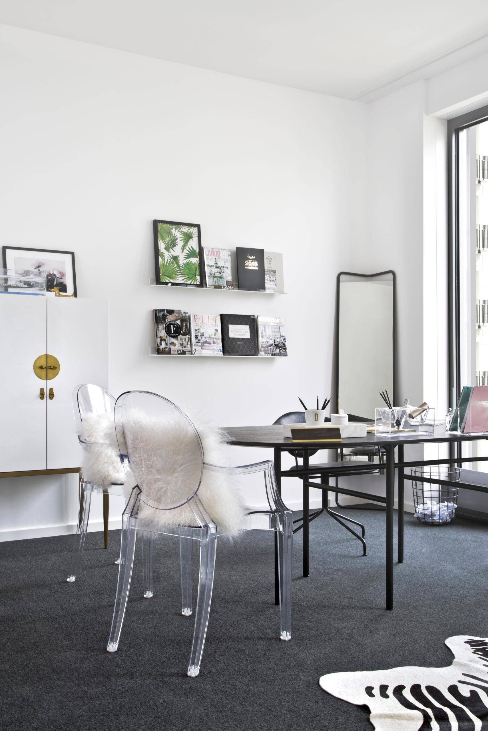 Lichte woonkamer met fotolijstjes op wandplank en transparante stoel met schapenvacht