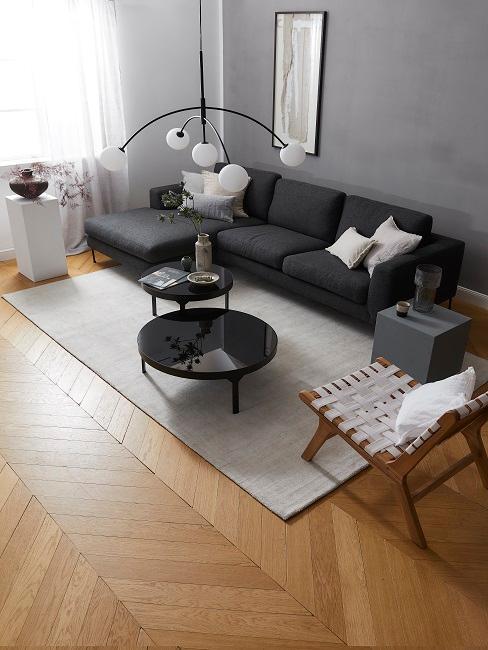 bank in de kleur zwart met een houten stoel wit kleed en witte kussens