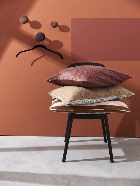 Terracotta kleur muur met een zwarte kruk met een stapel rode kussens