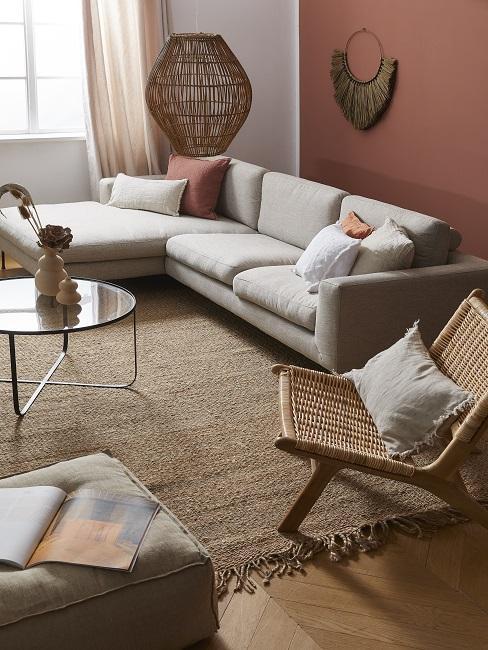 Terracotta kleur muur met een grijze hoekbank en houten stoel met ronde salontafel