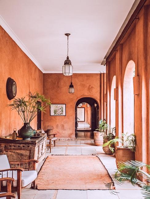 Terracotta kleur muren in een hal met zwarte hanglampen