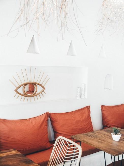 Terracotta kleur kussens met wit kunstwerk met houten tafels