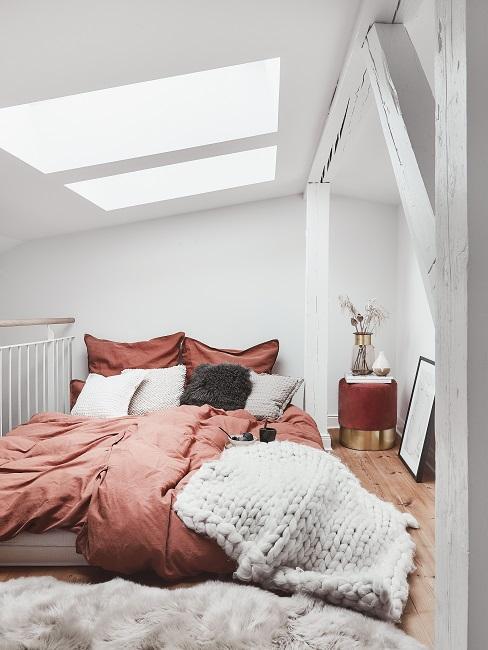 Terracotta kleur dekbed met witte en grijze kussens in een witte kamer