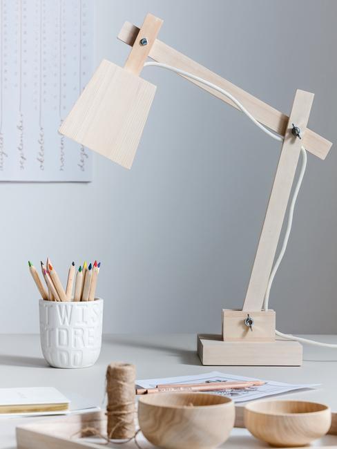 Clean desk met een houten lamp en witte pennenhouder