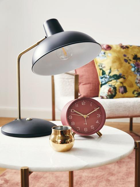 witte ronde tafel met een zwarte lamp en roze klok
