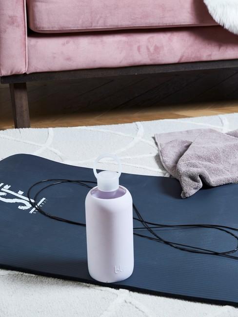 blauwe yogamat met waterfles op een wit kleed en roze bank