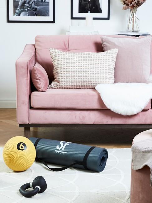 roze bank met een wit kleed en sportspullen