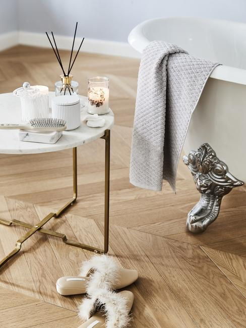 wit ligbad met zilvere poten en een ronde marmere tafel met geurstokken