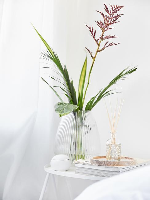 glazen vaas met een bloem op een witte tafel
