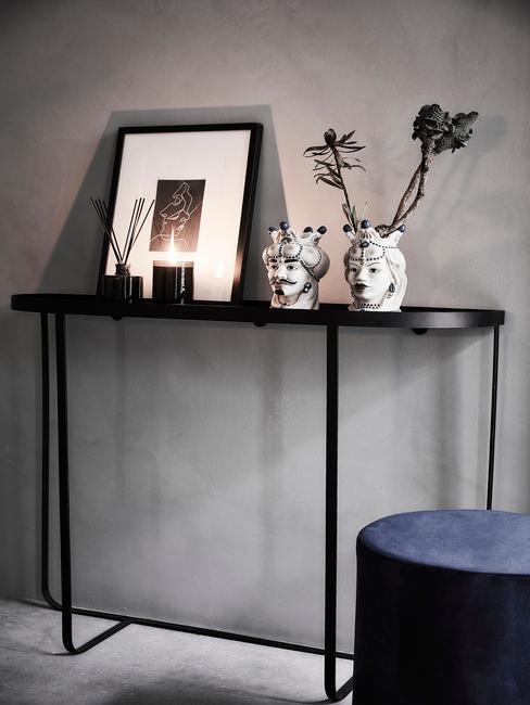 zwarte wandkast tegen een grijze muur met een blauwe poef en witte vazen