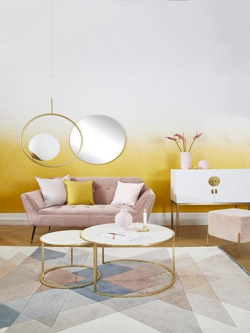 muur in de kleur geel met een roze bank en een goud met witte salontafel