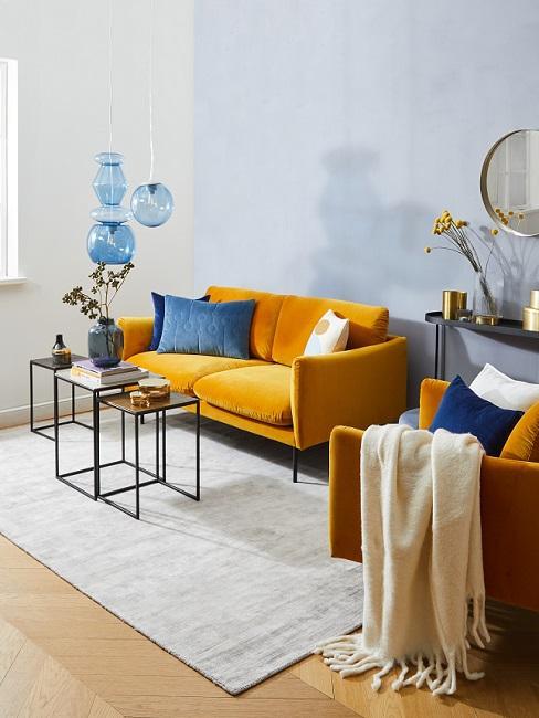 bank in de kleur geel met blauwe kussens en leren stoel