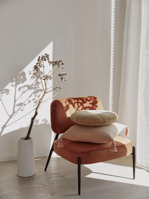oranje stoel met beige kussens en witte vaas met droogbloem