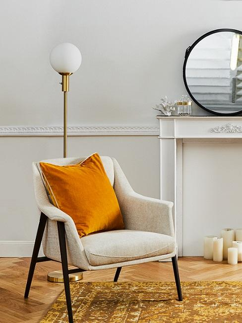 beige stoel met zwarte poef en oranje kussen