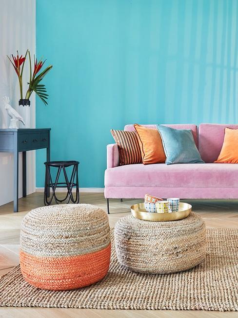 blauwe muur met een roze bank met oranje kussens en rieten met oranje poef
