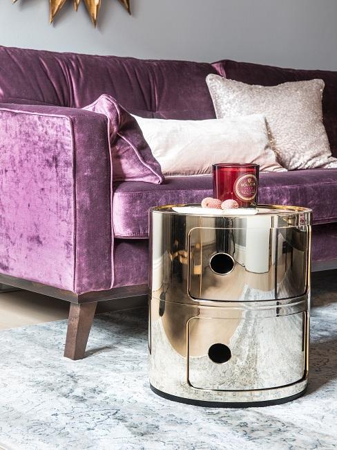 Een bank in de kleur paars met een gouden ronde tafel en roze kussens