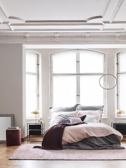 grijs bed met een dekbed in de kleur paars