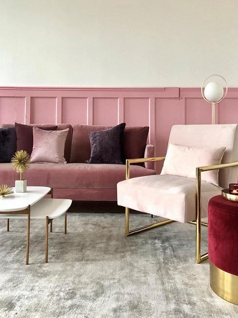 roze bank tegen een roze muur met kussens in de kleur paars