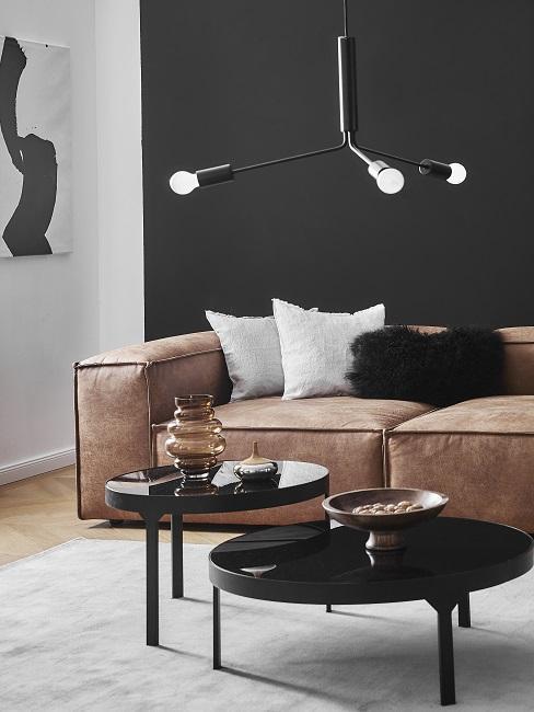 Zwarte muut met bruin leren blok bank met ronde zwarte salontatafels op wit vloerkleed