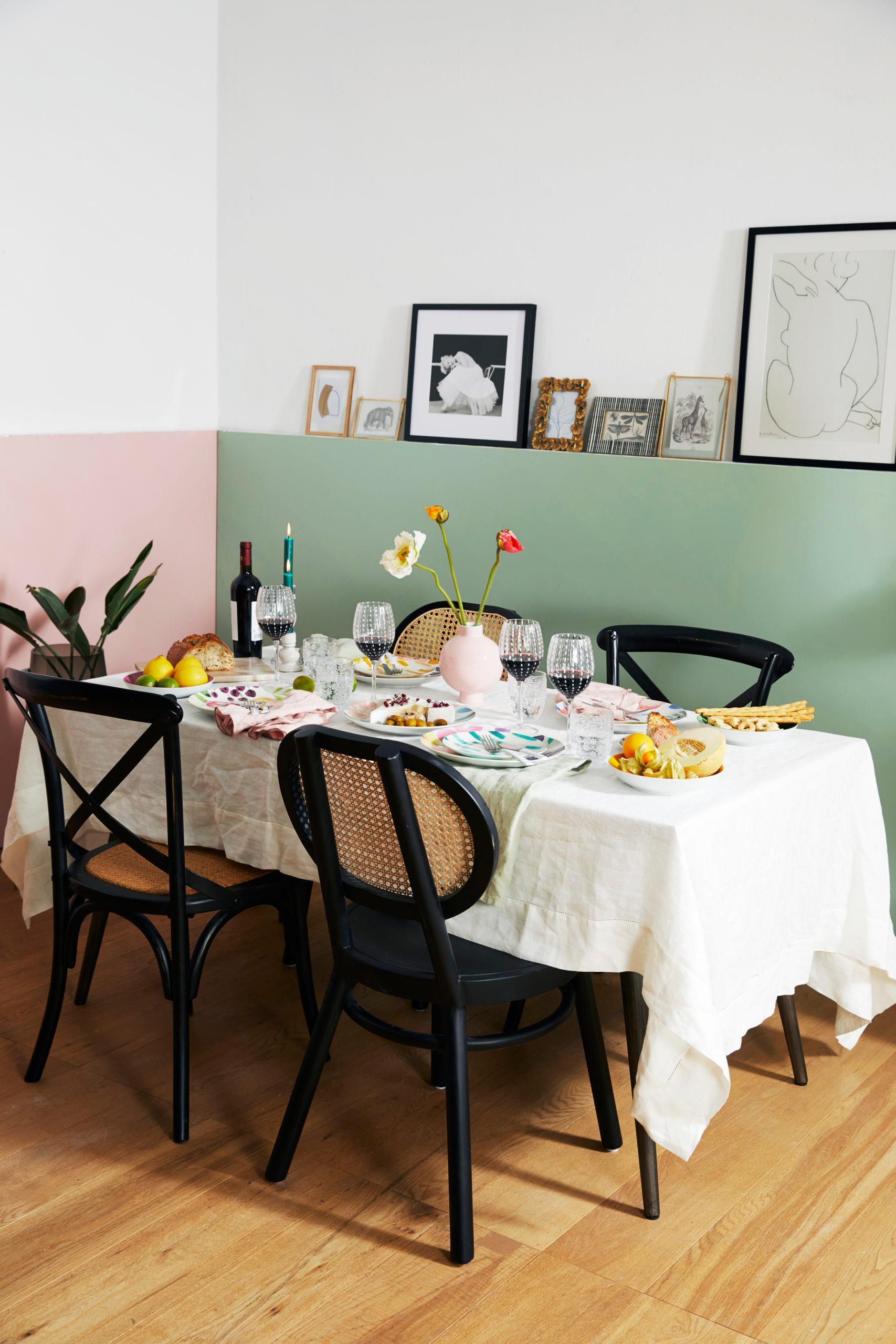 Oranje en groen witte muur met eetkamertafel met rotan stoelen