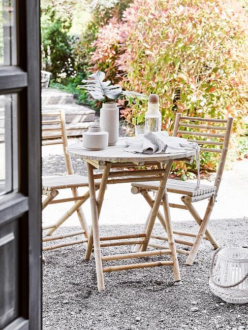 Vanuit de achterdeur een inkijk vanuit een ronde tafel met houten stoelen