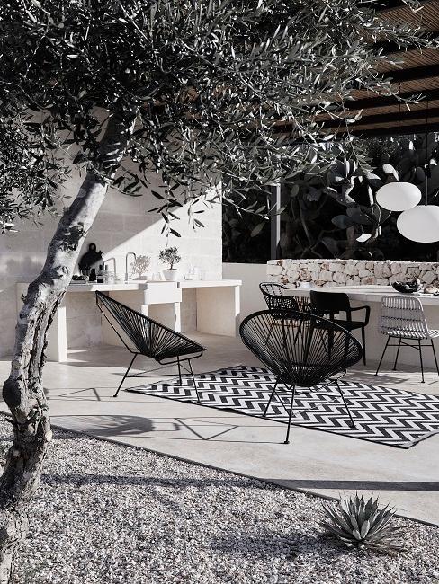 Zwart wit achtertuin met zwarte meubels en grijze tegels met geblokt vloerkleed
