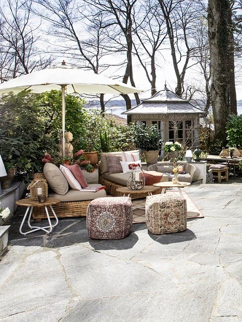 Tuin met grote grijze tegels witte parasol en bruine rieten meubels
