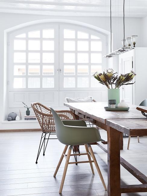 Houten eettafel met verschillende eetkamerstoelen voor witte openslaande deuren