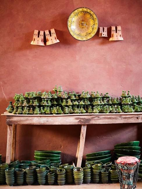 Terracotta muur met houten tafel en beelden