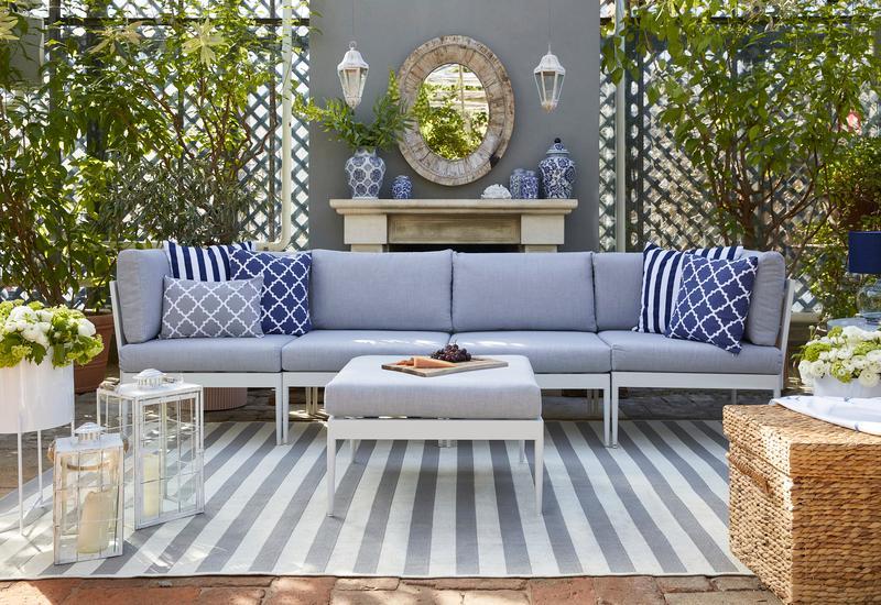 witte outdoor loungebank met blauwe kussens