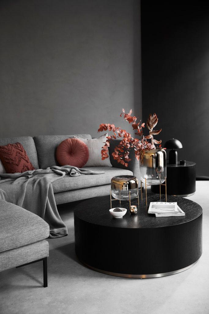 Grijze ruimte met grijze wanden, bank en vloer met zwarte salontafel rond en witte accessoires