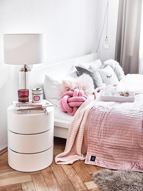 roze sprei op wit bed met witte lamp