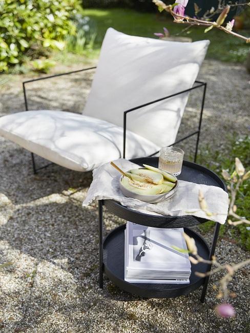 Witte lounge stoel met zwarte stalen details en zwarte bijzettafel op grind