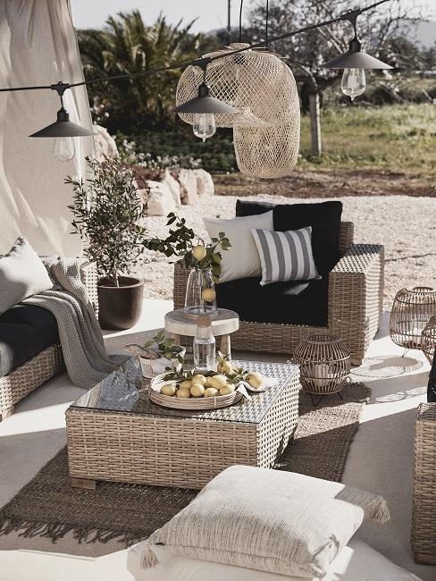 Mediterrane tuin met rieten grove meubels en buitenlampen