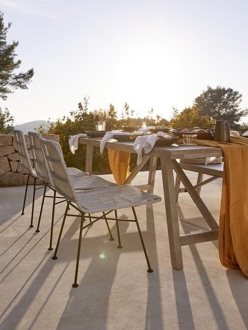 Mediterrane tuin met houten tuinmeubels en rotan stoelen bij een ondergaande zon