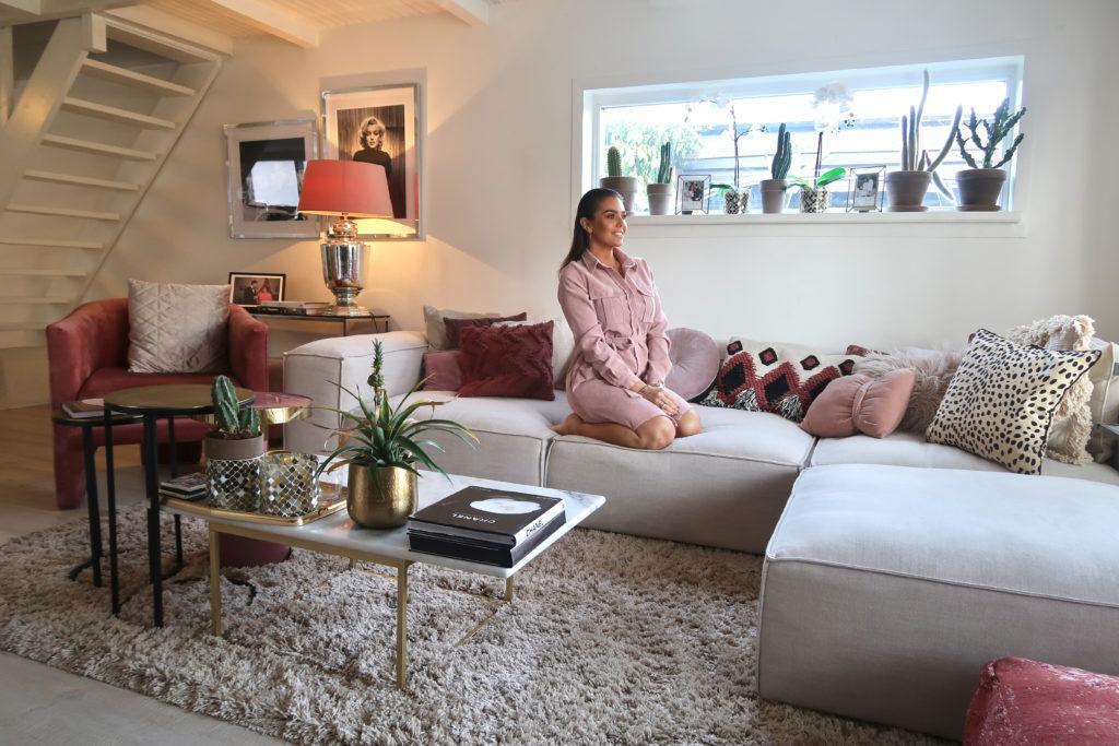 Laura Ponticorvo in haar woonkamer zittend op haar grijze lennon bank