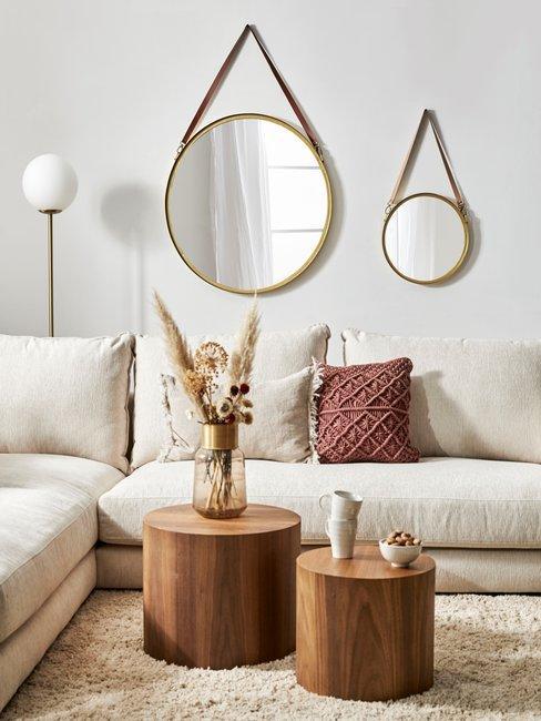 Homestories zandkleurige hoekbank met hoogpolig vloerkleed met ronde houten salontafels en ronde spiegels aan de muur