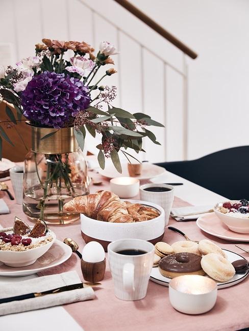 Moederdagontbijt met paarse bos bloemen in vaas op tafel met oatmeal en oud roze tafelloper