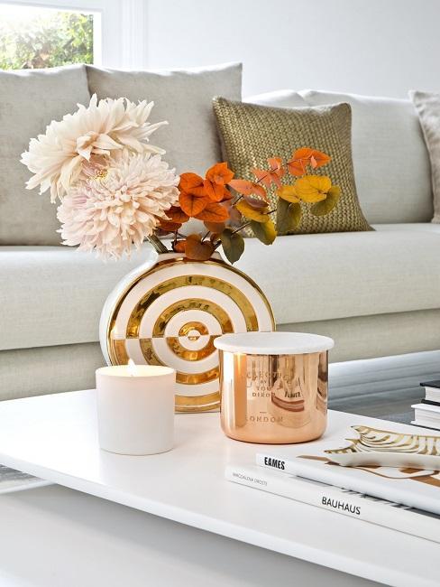 Oranje bloemen in een goud met witte vaas op een witte salontafel