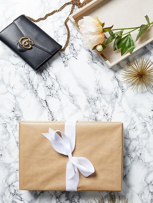 Cadeau met witte strik en gucci handtas op marmeren ondergrond