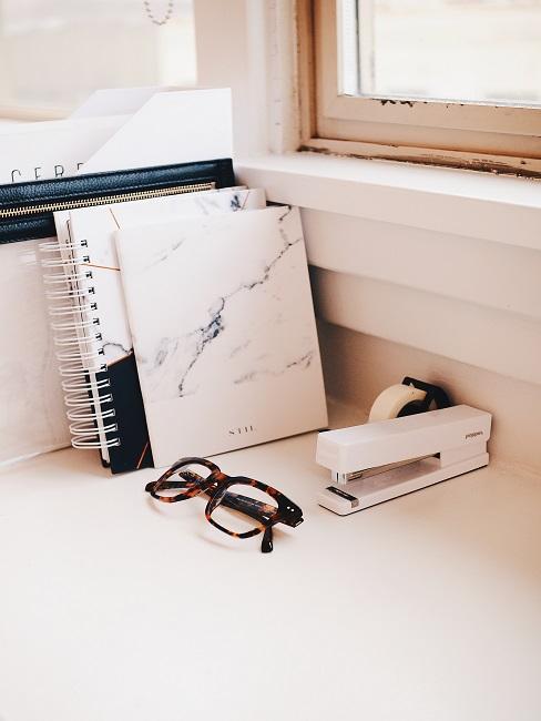 Staande boeken en tijdschrijft op een tafel onder raam