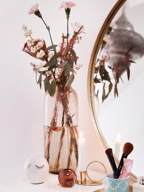 Make up tafel met ronde spiegel en bloemen in een doorzichtige vaas